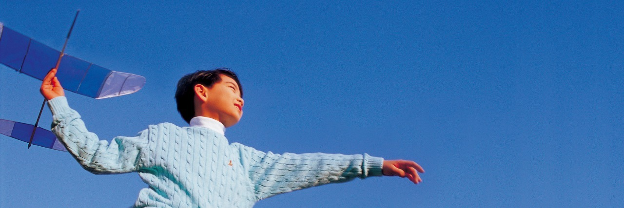 boy playing with toy plane against sky background