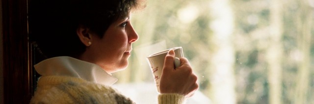 woman in sweater drinking tea by the window