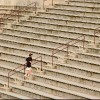 college athlete running up empty bleachers