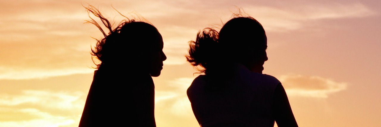 Silhouette of two women in front of a sky at sunset