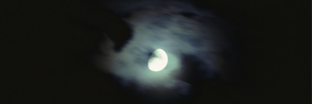 A full moon emerging from behind clouds