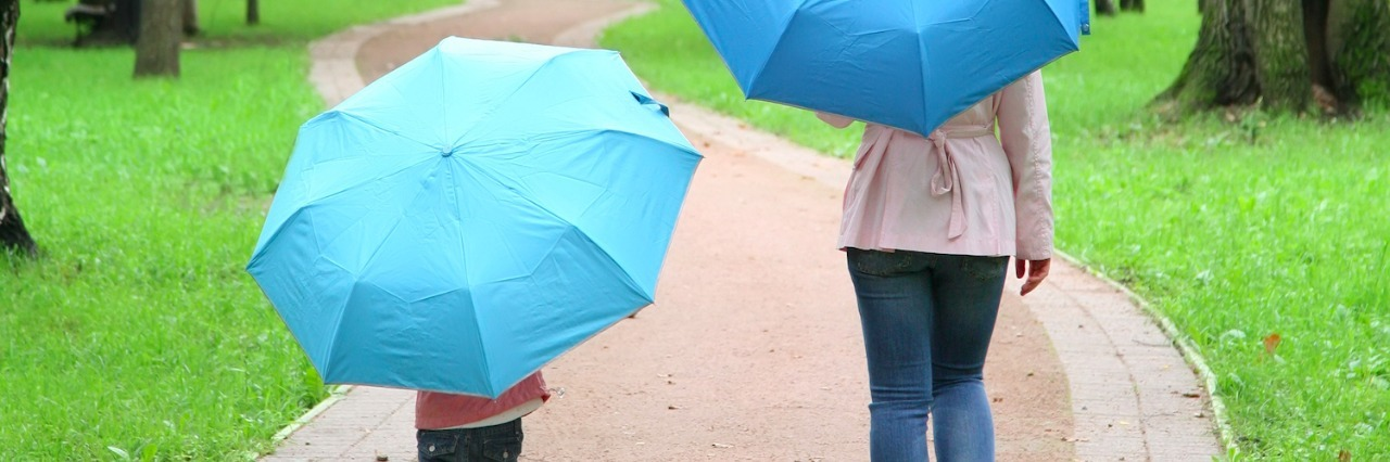 mother and child holding umbrellas, walking on a path in the park