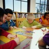 Children coloring with crayons at table in classroom.