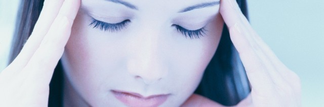 close-up of a woman rubbing her temples with eyes closed