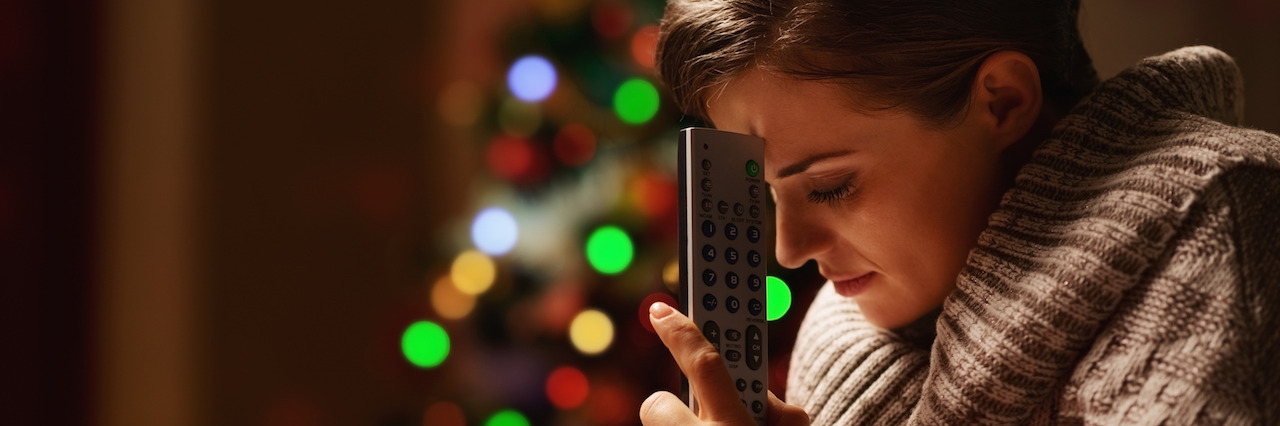 Frustrated young woman with tv remote control in front of christmas tree