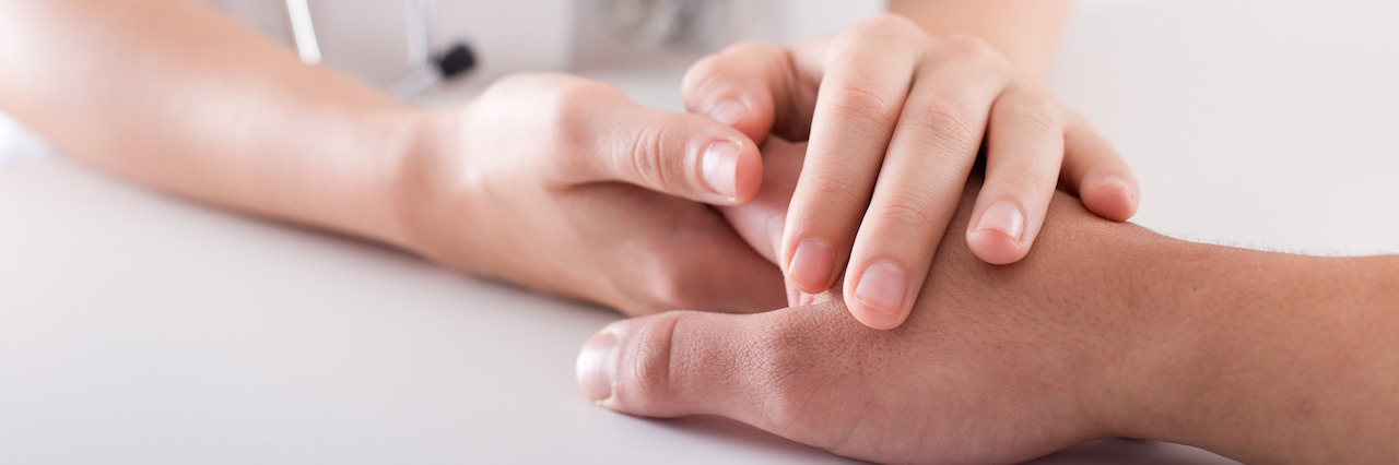 Close up of young female hands holding patient's hand as support