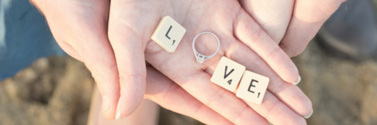 Letter Tiles and Engagement Ring in Hand