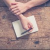 Close up on the hands of a young woman as she is writing in a small notepad at a wooden table