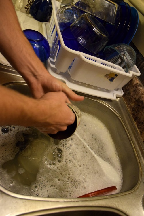 person washing dishes in the sink