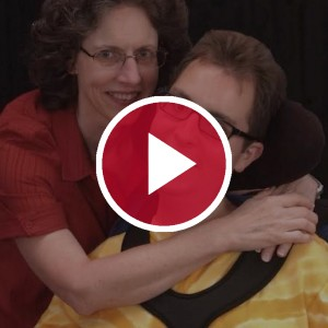 Mother and son with muscular dystrophy behind a red video play button