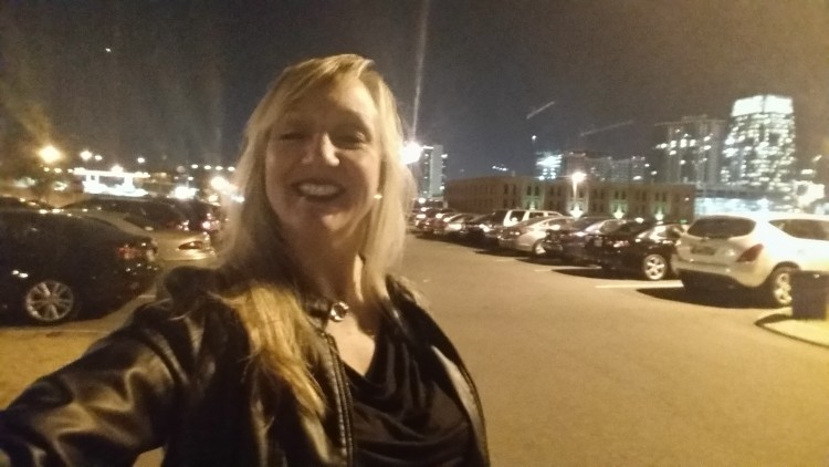 woman taking a selfie outside in the city at night
