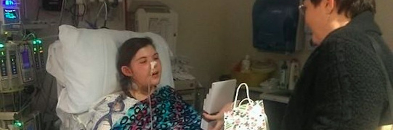 girl in hospital bed being given gifts
