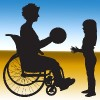 Person in a wheelchair playing ball with a child.