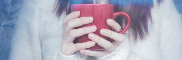 woman wearing white sweater and holding red coffee mug
