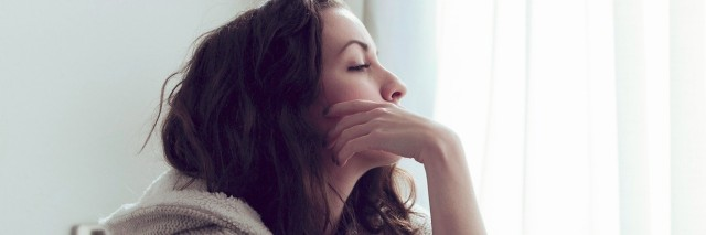 woman sitting on bed thinking and looking out window