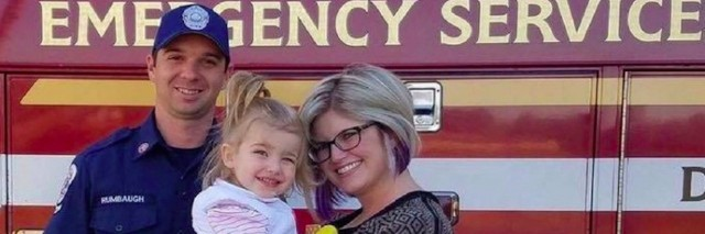 mother daughter and firefighter in front of fire truck