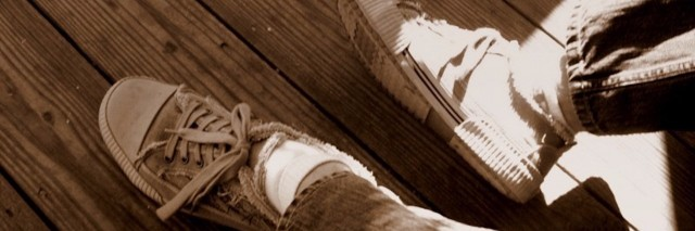 a person's feet wearing old sneakers against a wooden floor with sunlight hitting the feet