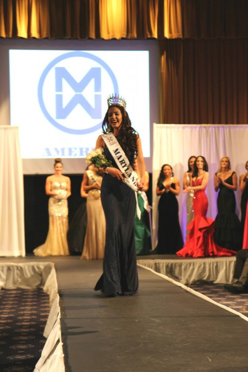 the author wears a dress and a pageant sash, and walks down a runway
