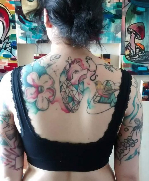 colorful tattoo across back of shoulders and upper arms
