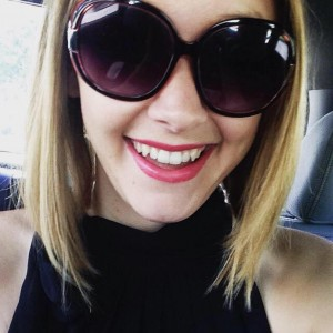 selfie of a blond woman in the car wearing sunglasses and red lipstick