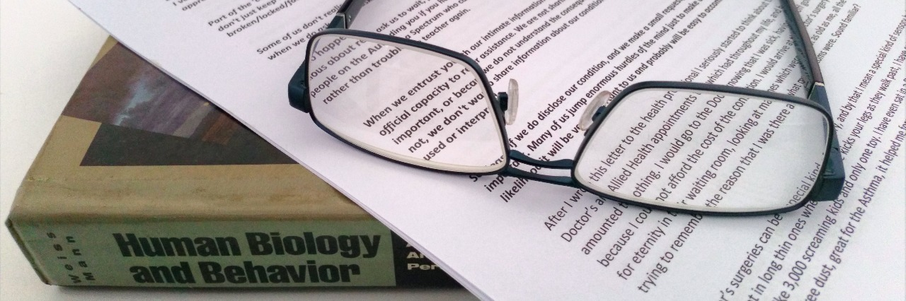 a pair of glasses lying on an essay and a textbook