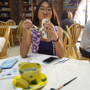 girl sitting at table painting pottery