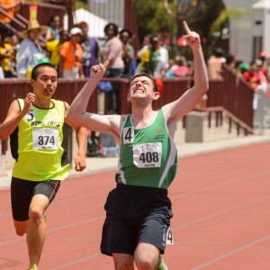 Runner running to the finish line with his hands triumphantly raised.