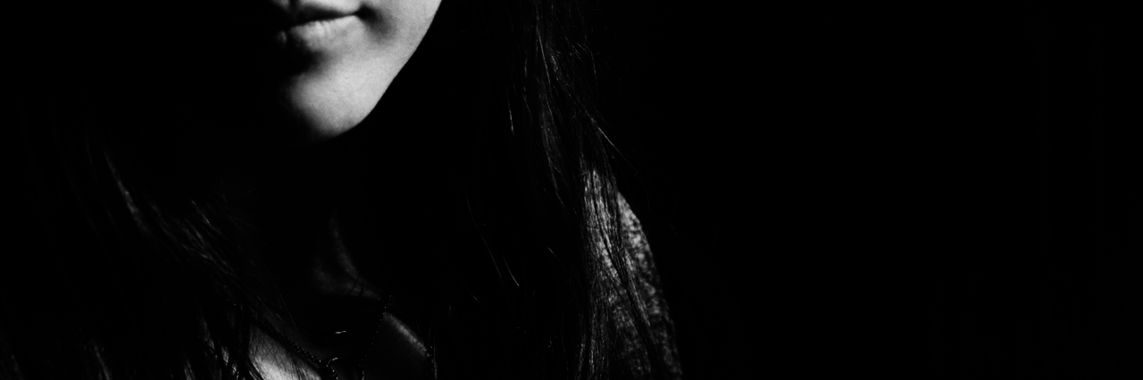picture of half a woman's face, black and white, slight smile