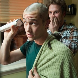 "An actor in the movie ""50/50"" struggling with cancer shave his head with a friend watching in the background."