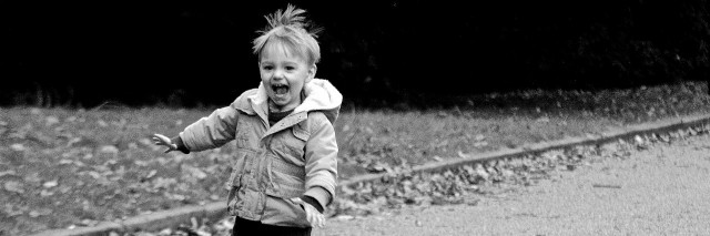 black and white photo of little boy running down road