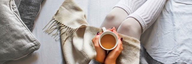 young woman sitting on a bed holding a cup of hot coffee on a cold winter morning at home