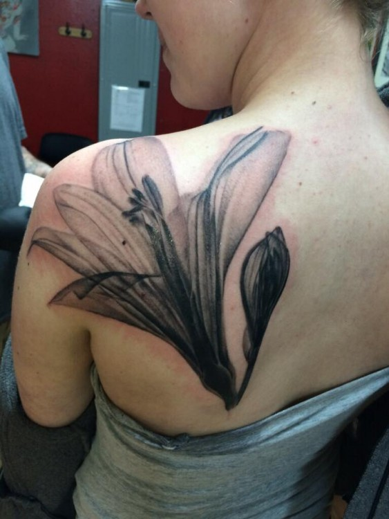 A tattoo on a woman's shoulder of an X-ray of a tattoo