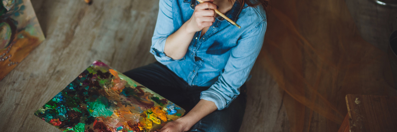 Female artist sitting with her brush and painting