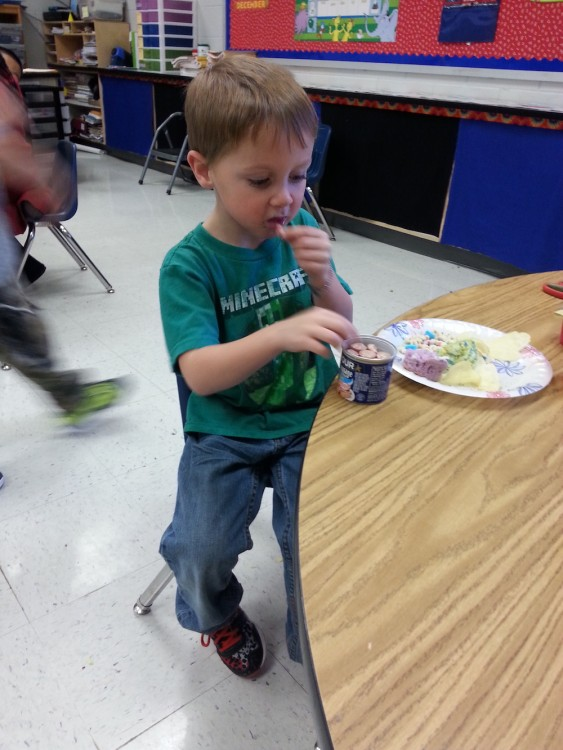 Young boy named Cayden eating a snack at school