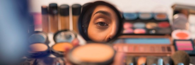woman looking in compact mirror before putting on makeup