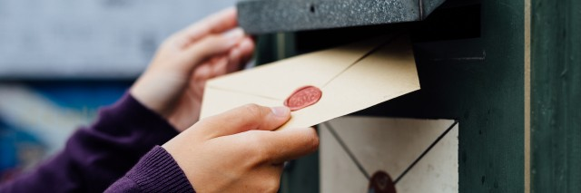 A woman's hands placing a letter in a mailbox