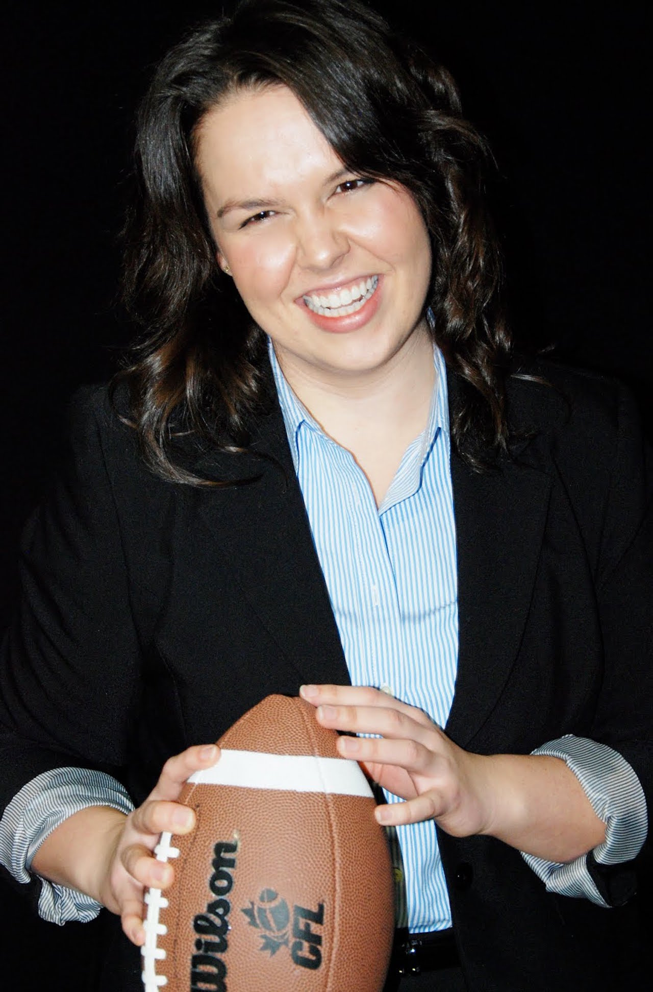 woman smiling with a football