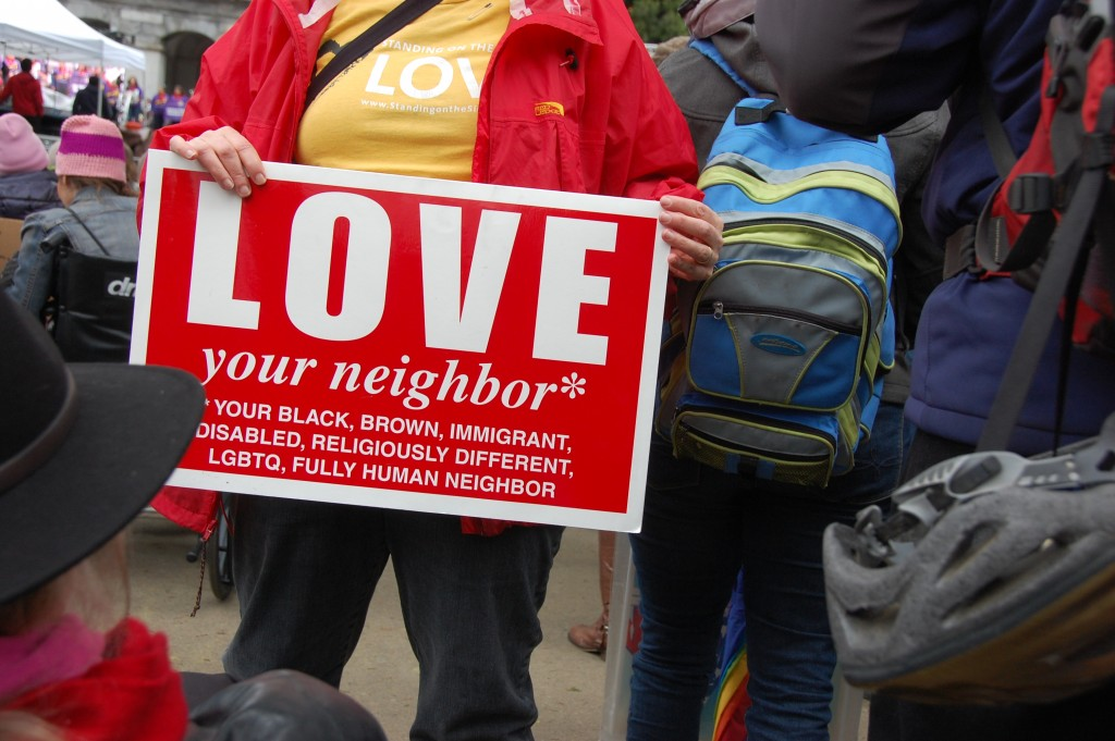 "Woman carrying a ""love your neighbor"" sign listing various groups including disability."