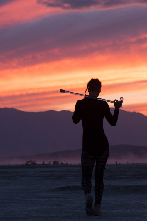 silhouette of woman walking with her cane in a valley looking at mountains and sunset