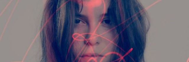 A double exposure image of a woman's face and red lights shining on her