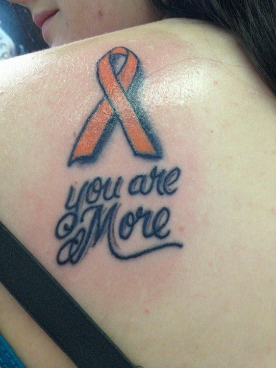 "A tattoo of an orange ribbon and text that says, ""You are more."""