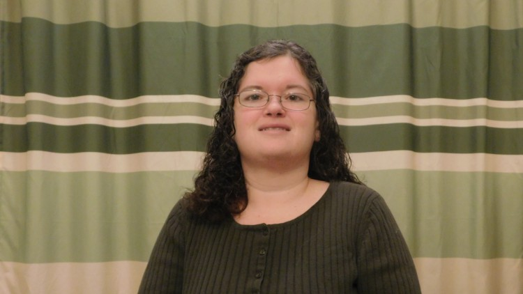 woman in dark shirt and glasses smiling in front of striped green curtain