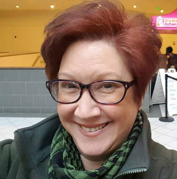 woman with red hair and glasses taking a selfie