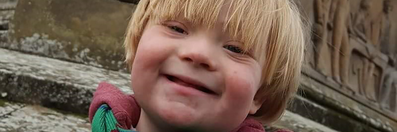 Rory, a little boy with Down syndrome who is wearing a maroon winter coat and green striped scarf.