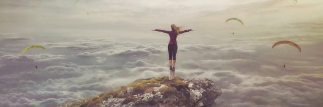 surreal picture of woman on rock with upside down city in sky