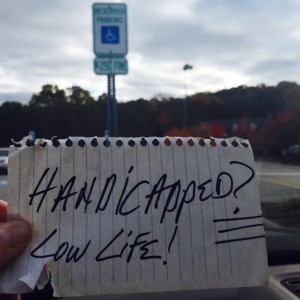woman holding a note that someone left on her car that says Handicapped? Low Life!