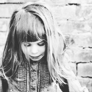 Black and white photo of child in front of brick wall