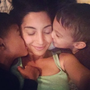 twin sons kissing their mothers cheeks from each side