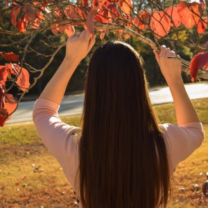 woman with long brown hair standing outside under a branch with autumn leaves