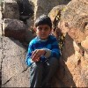 young boy sitting amongst rocks